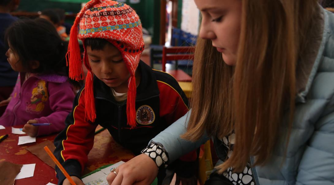 Childcare volunteer in Peru helps a kid during arts and crafts activity as part of her volunteer work for teenagers.
